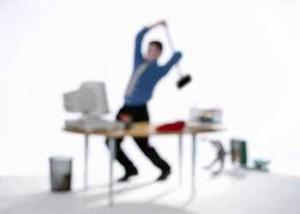 Mann mit erhobenem Hammer vor Rechner (Microsoft Clip Art)